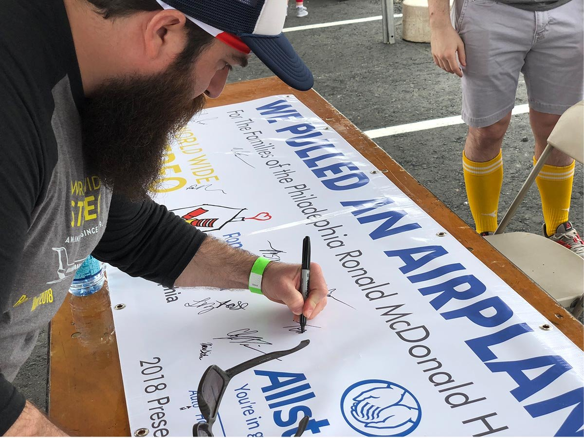 Tommy signs the plane pull banner