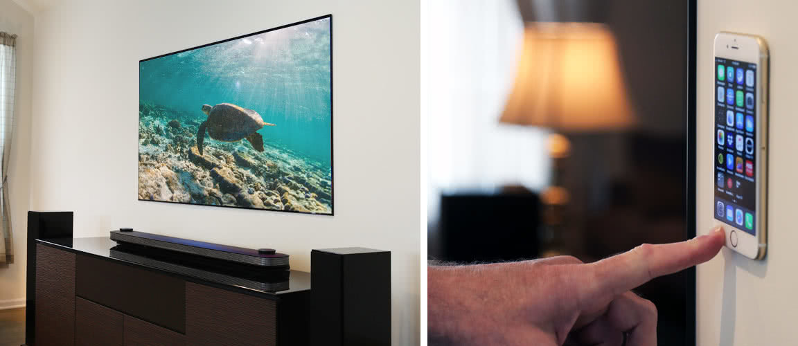 LG OLED77W7P Wallpaper TV rests flush against the wall and pictured against an iPhone