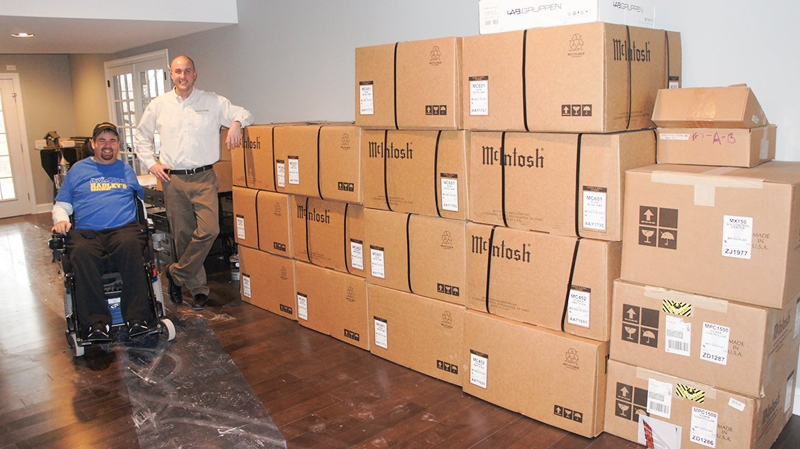 Client and System designer standing next to McIntosh boxes